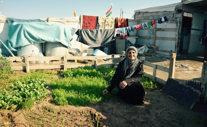 Syrian gardener poses with her garden at Domiz camp, Iraq